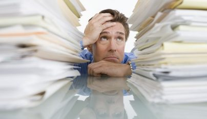 Businessman Overwhelmed with Paperwork --- Image by © Royalty-Free/Corbis