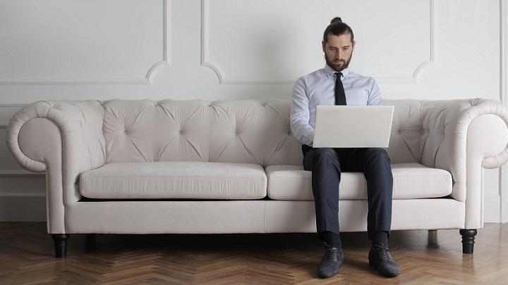 hombre-con-ordenador-sentado-en-sofa