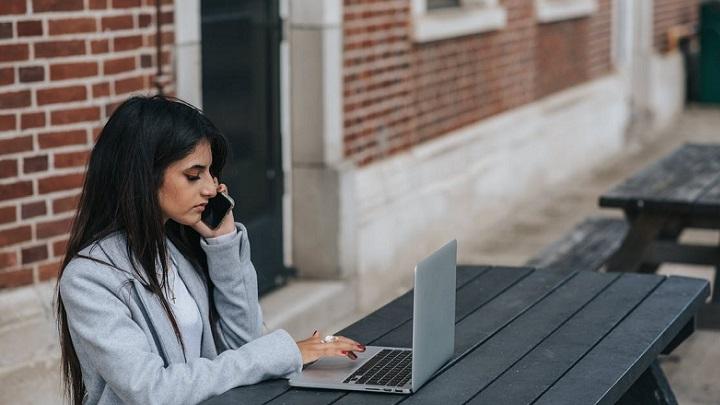 chica-habla-por-telefono-delante-del-ordenador